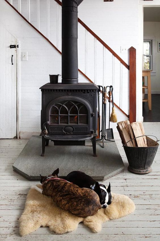 a modern farmhouse space with a vintage black wood burning stove and a cozy rug next to it