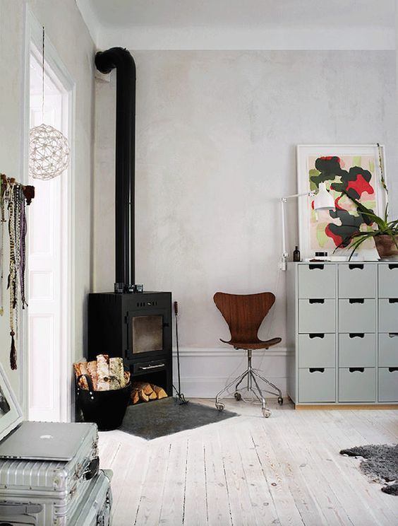 a Scandinavian room with a cozy wood bruning stove in the corner and some firewood next to it