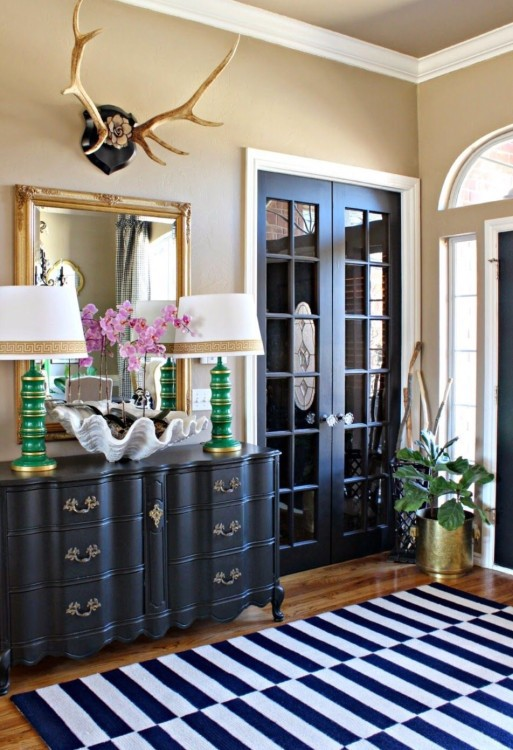 black French doors, a black sideboard and a navy and white striped rug create a cohesive look in the space