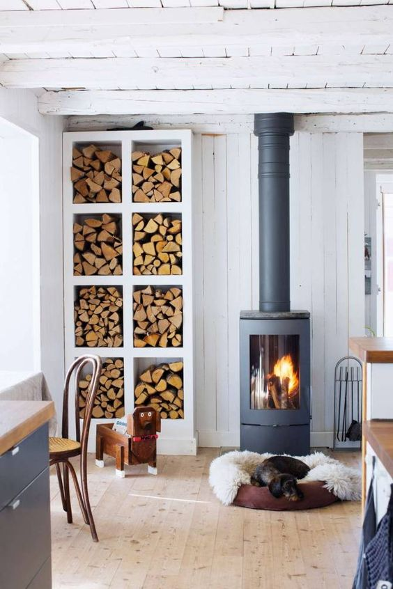 a Scandinavian space with a modern and cool wood burning stove plus an elegant open storage unit for firewood