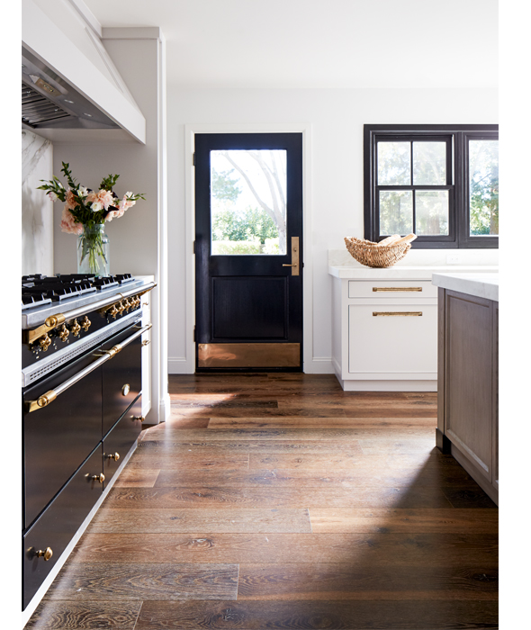 a chic kitchen with a touch of art deco - a black and gold cooker and a matching door and black frame windows