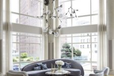 20 an elegant double-height living room with a curved blue sofa and matching chairs plus gold touches here and there