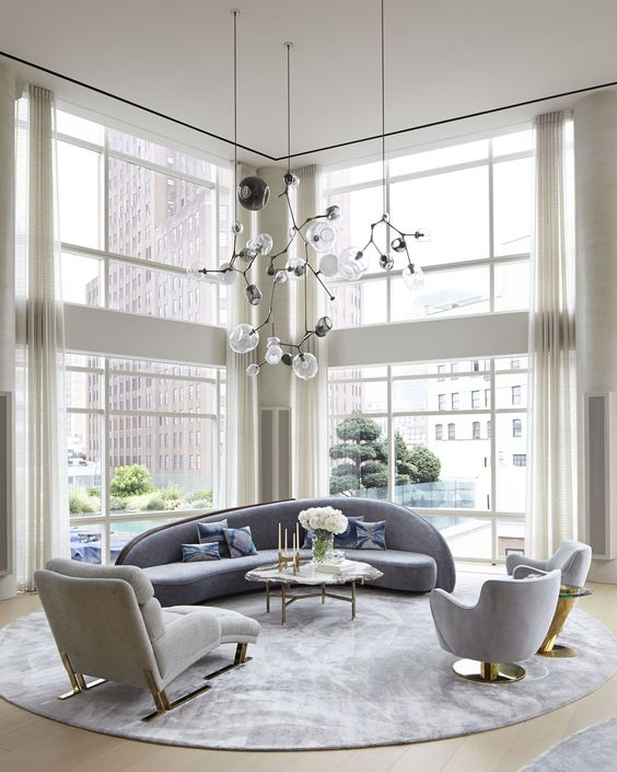 an elegant double height living room with a curved blue sofa and matching chairs plus gold touches here and there