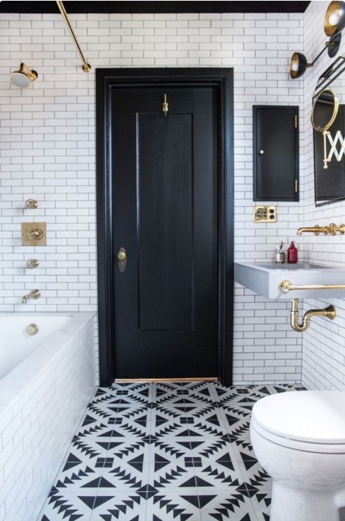 a chic monochromatic bathroom with patterned tiles, a black door and a ceiling for a bold look