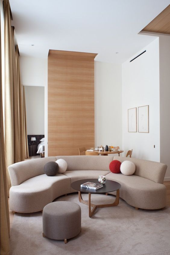 a small living room made bolder with a curved sofa that also separates the living room and the dining space