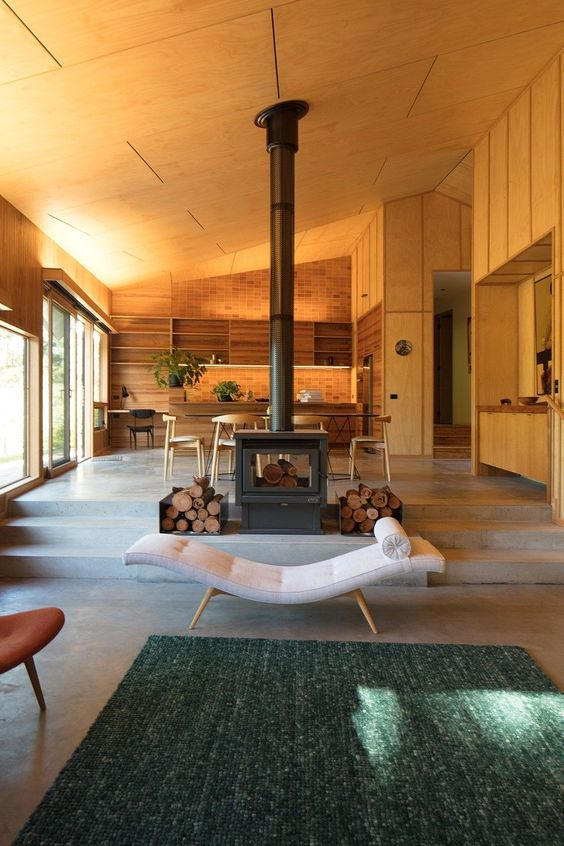 a stylish wood burning stove with some firewood can work as a cool space divider that cozies up the spaces