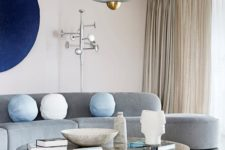 22 a neutral living room made bold with a curved grey sofa, a navy artwork and a marble coffee table and a cork stool