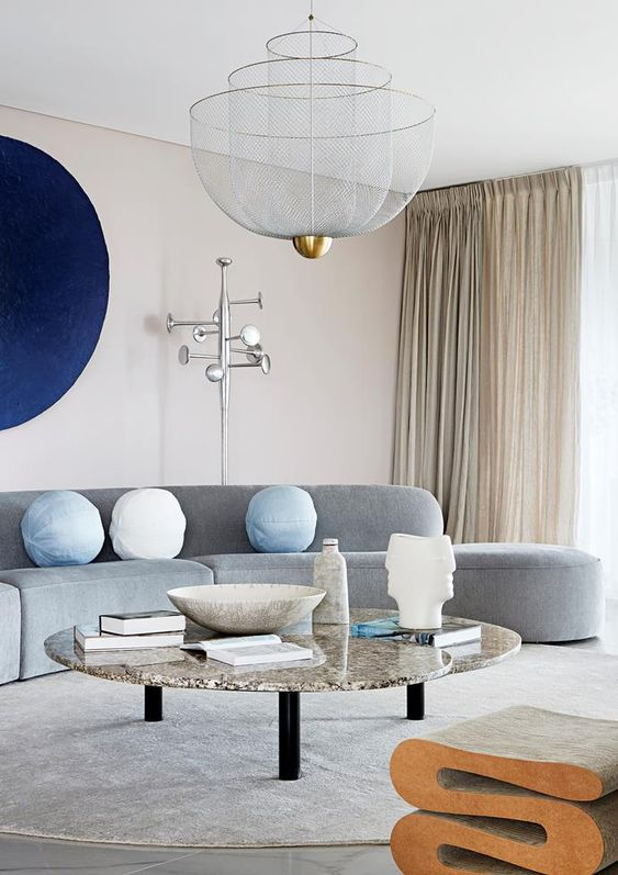 a neutral living room made bold with a curved grey sofa, a navy artwork and a marble coffee table and a cork stool