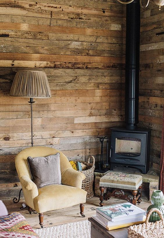 a vintage meets rustic reading nook with a wood burning stove, vintage furniture and reclaimed wood walls