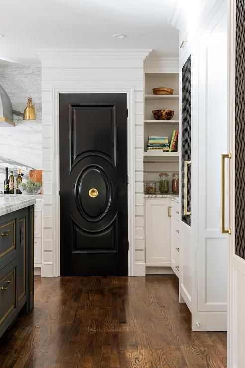 a chic black door echoes with the kitchen island done in the same color creating a bold and chic look