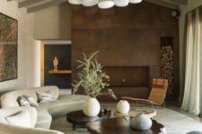 23 a chic living room with a long white curved sofa, a wood slice coffee table and a metal clad fireplace