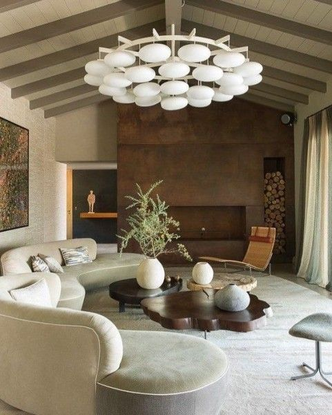 a chic living room with a long white curved sofa, a wood slice coffee table and a metal clad fireplace