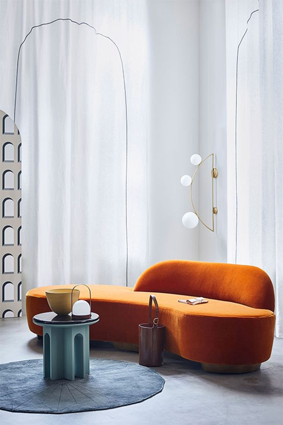a  bold conceptual living room with a curved orange sofa, a round blue rug and a turquoise table for a bold setup