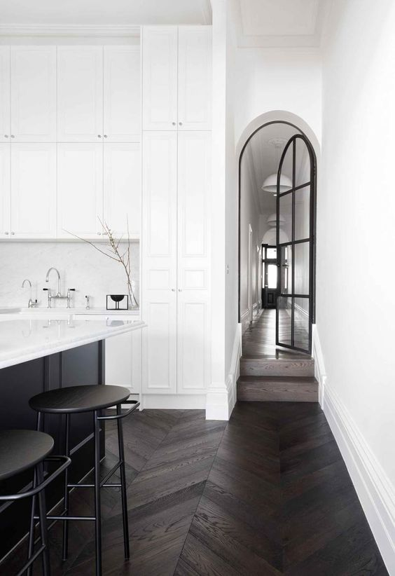 an arched black French door, a black kitchen island and stools that continue the dramatic theme of the decor