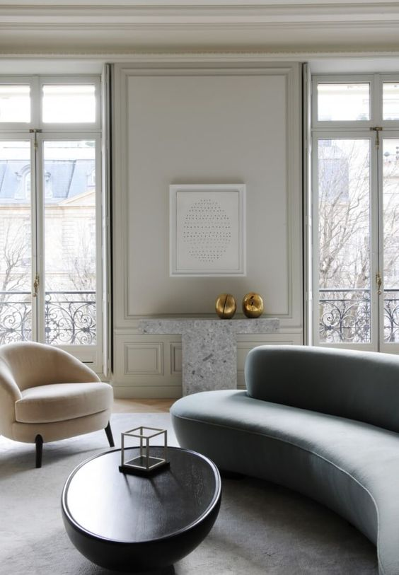 an exquisite minimalist living room with a grey curved sofa and a matching white chair plus a curved table to soften the space