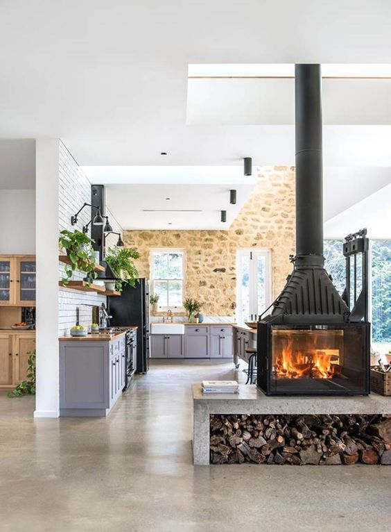 an oversized wood burning stove on a concrete platform with firewood divides the spaces in a cozy way
