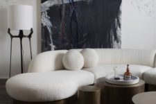 26 a monochromatic living room with a creamy curved sofa and round pillows and dark metal round tables