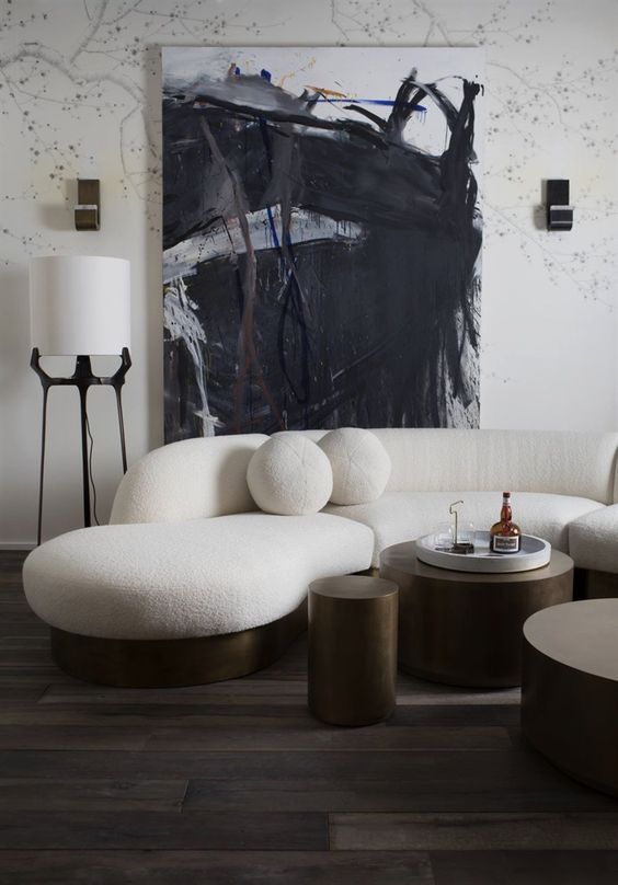 a monochromatic living room with a creamy curved sofa and round pillows and dark metal round tables