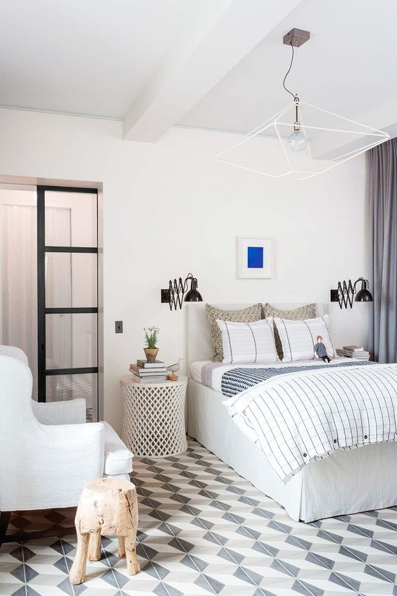 a statement geometric chandelier is paired with wall sconces and make the bedroom more welcoming