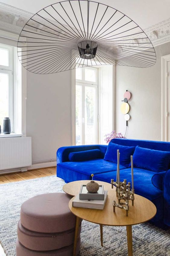 a luxurious living room with a cobalt blue velvet sofa that is the main centerpiece in the room