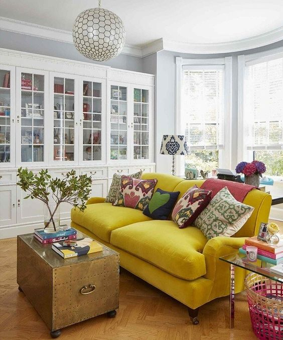 a bold mustard velvet sofa is the main decor piece in this space, and it brings color to it