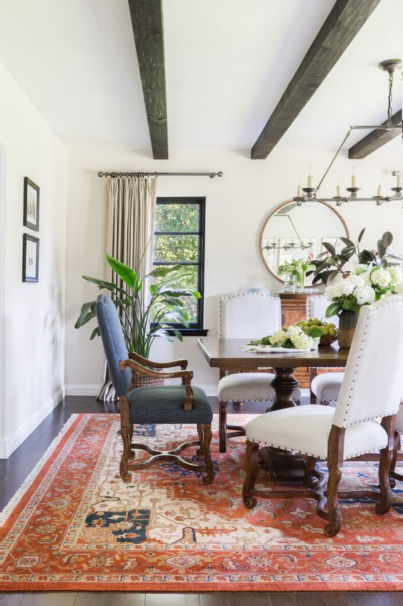 a Spanish dining room with heavy dark wooden furniture, a printed rug, a round mirror and lots of greenery and blooms
