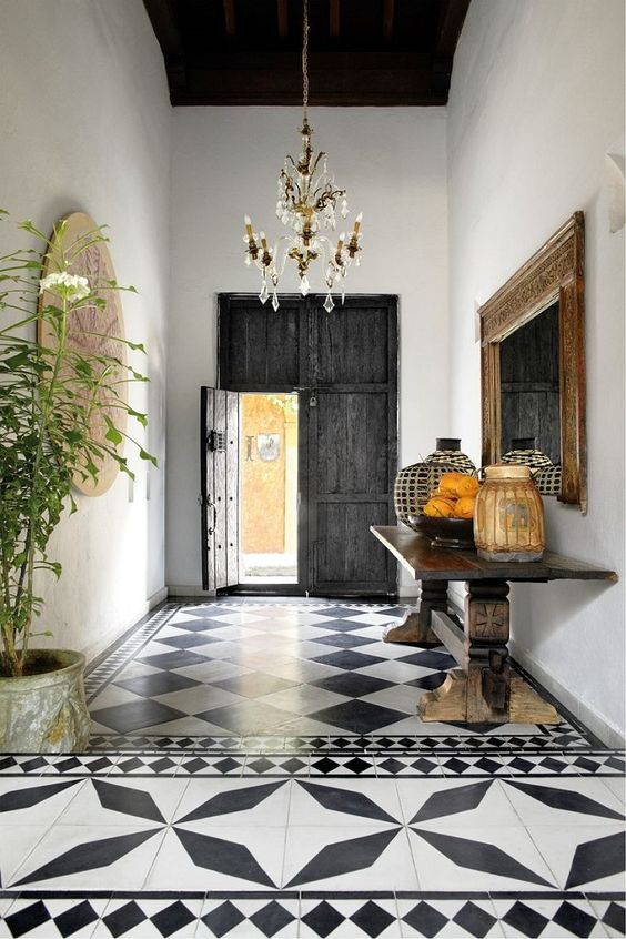 a Spanish entryway with black and white printed tiles, a reclaimed dakr wood door, a heavy console and potted greenery