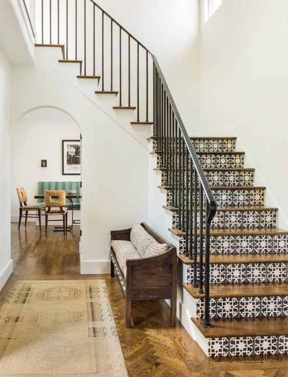 a Spanish-inspired space with printed tiles on stairs, wooden furniture and floors and wrought railing