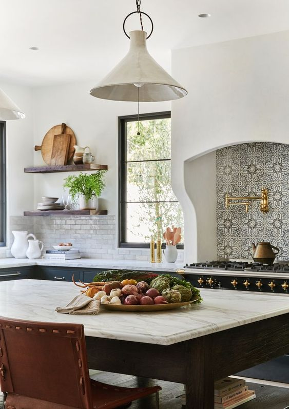 a Spanish kitchen with a large cooker, a printed backsplash, gold touches, dark furniture and lamps with a vintage feel