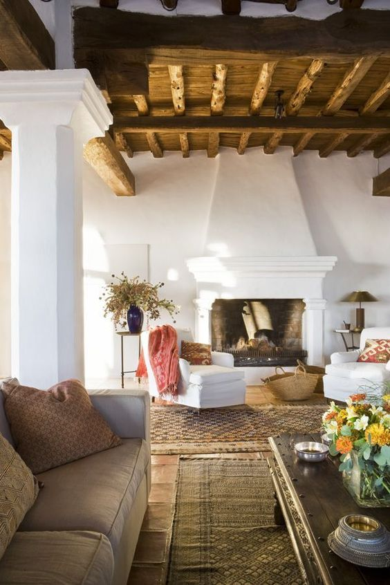 a Spanish living room with a wooden ceiling with beams, white walls and a fireplace, neutral furniture and dried blooms