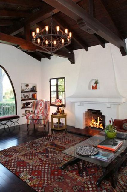 a Spanish living room with white plaster walls, a dark ceiling with beams, a large fireplace and pritned textiles and upholstery