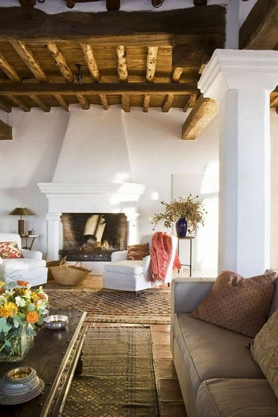 a Spanish living room with white plaster walls, wooden ceiling with beams, layered rugs and some fresh and bright accents