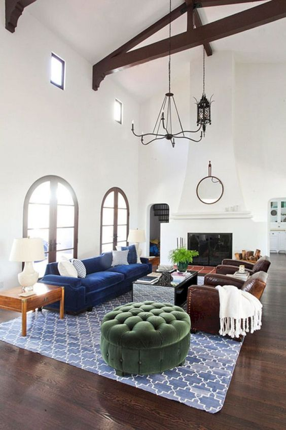 a Spanish living room with white walls and a double-height ceiling, dark wooden beams, a large fireplace and jewel tone furniture