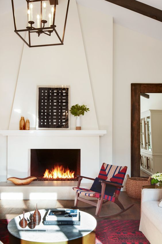 a Spanish living room with white walls and a large fireplace, printed textiles in bold colors and warm-colored artworks