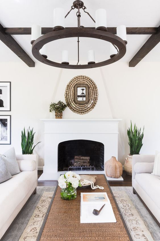 a Spanish living room with white walls, dark wooden beams, a matching chandelier, a fireplace and natural touches