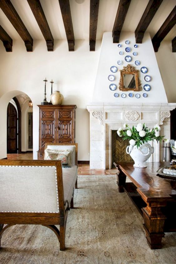 a Spanish living room with white walls, tiled floors, dark wooden beams, elegant and heavy furniture and a large fireplace