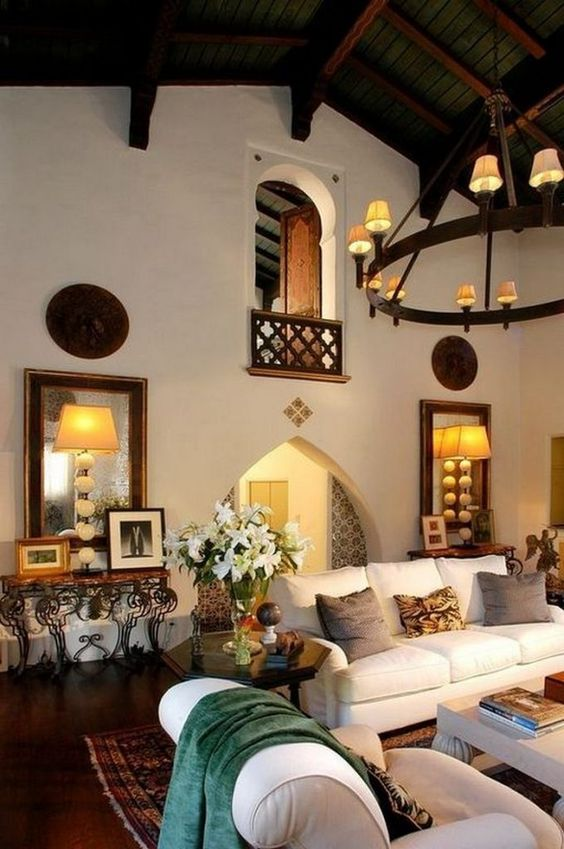a Spanish-styled room with white walls, arched doorways, neutral furniture, vintage lamps and chandeliers