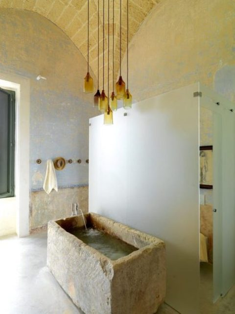 a beautiful bathroom with a rough stone bathtub and a cluster of amber glass pendant lamps