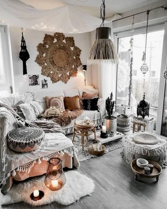 a boho Moroccan living room in neutrals, with a macrame rug, ottomans and throws, candle lanterns and lights