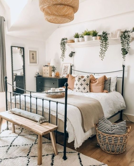 a boho bedroom with a forged bed, potted greenery, a wicker lamp, wooden furniture and dark touches