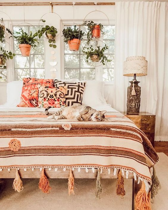 a boho bedroom with potted greenery suspended in hoops over the bed and cool printed and tassel textiles