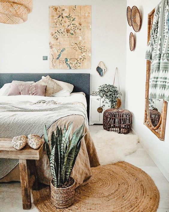 a boho bedroom with woven plates, a rattan mirror, a jute rug and a wicker lamp plus some plants