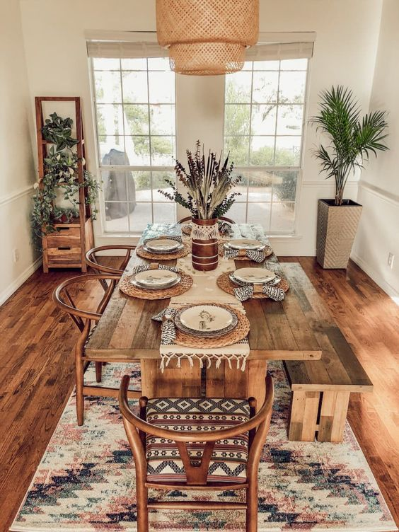 a boho dining room with a wicker lamp, reclaimed wood furniture, a boho rug and potted greenery plus macrame and wicker