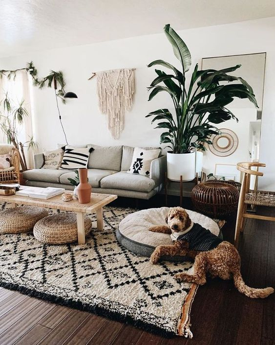 a boho living room with a macrame hanging on the wall, jute ottomans, prints and greenery in pots