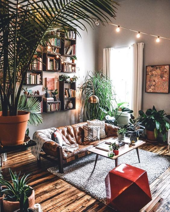 a boho living room with an arrangement of bookshelves, a leather sofa, lots of potted greenery and a geometric stool
