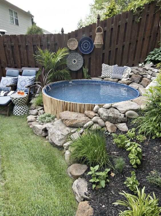 a boho outdoor space with planted greenery, boho decor, printed blue textiles and a small round pool clad with bamboo