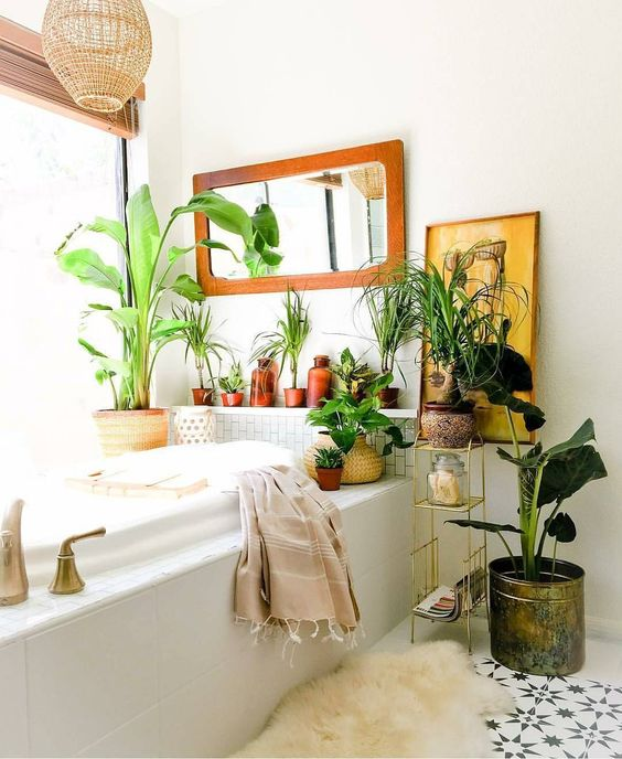 a boho space with potted greenery and plants, an artwork, a mirror and a wicker lampshade