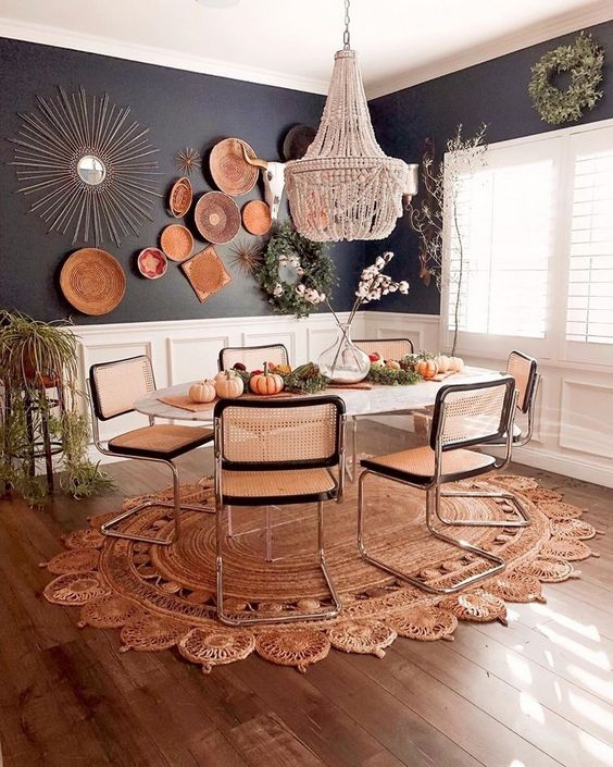 a bold boho dining room with a beaded chandelier, wicker chairs, a jute rug, decorative plates and greenery