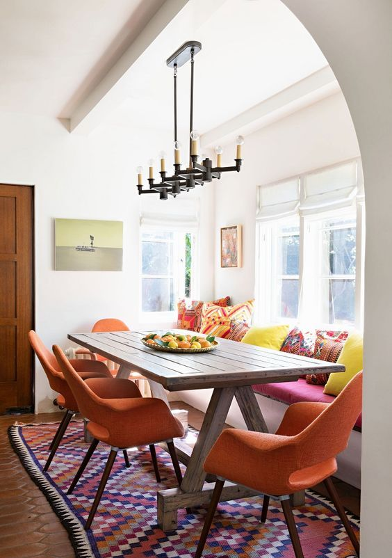 a bright and modern dining space in a Spanish space, bright pillows, warm-colored chairs, a wooden table and a vintage chandelier