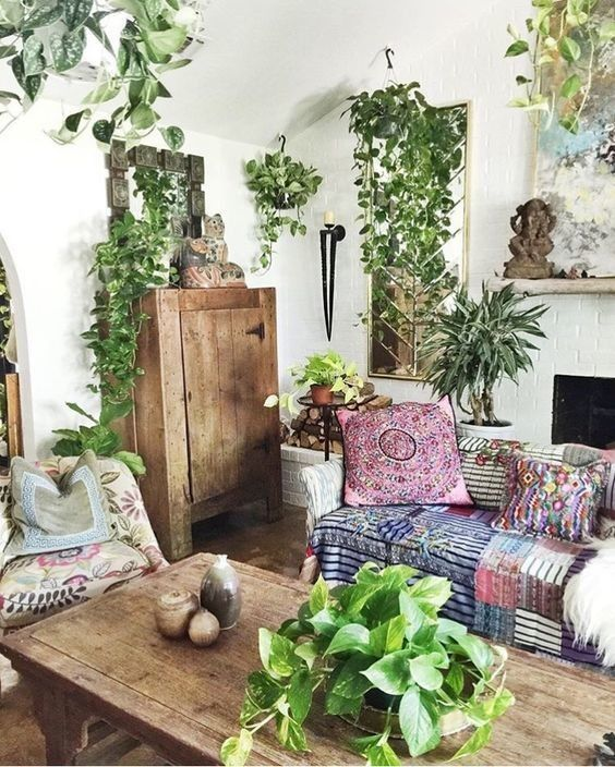 a bright boho living room with patchwork textiles, lots of potted greenery, rustic wooden furniture and a fireplace